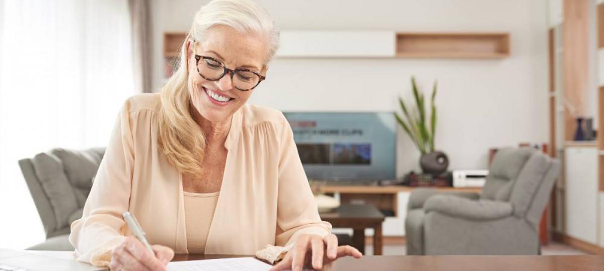 Femme calculant son taux d'endettement réduit après un rachat de crédit