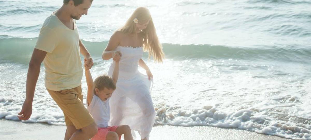 Famille heureuse se promenant au bord de la mer.