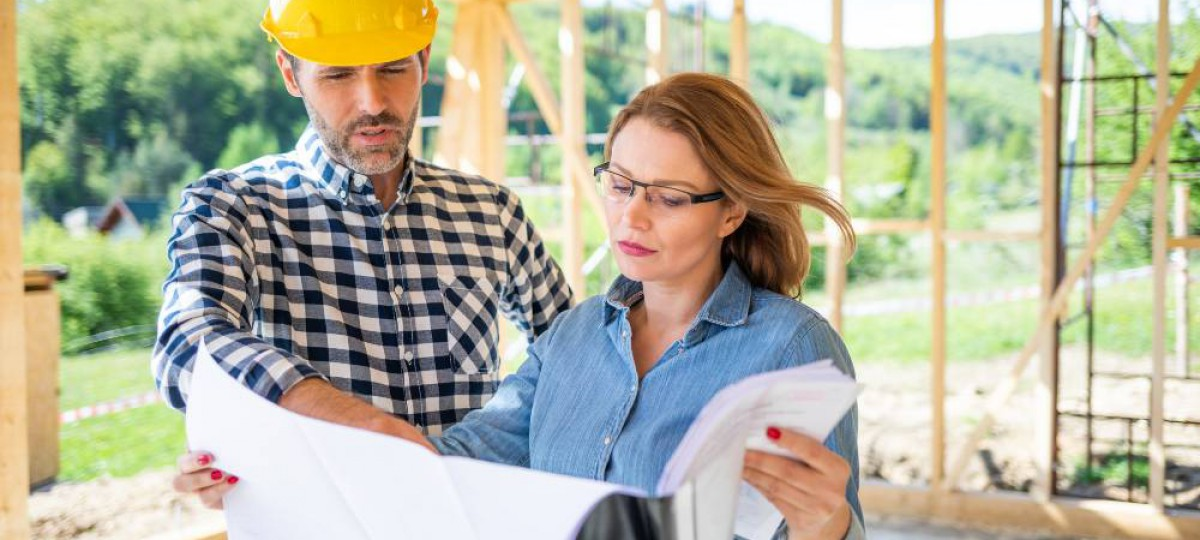 Propriétaire et chef de chantier examinant les plans d'une maison en construction
