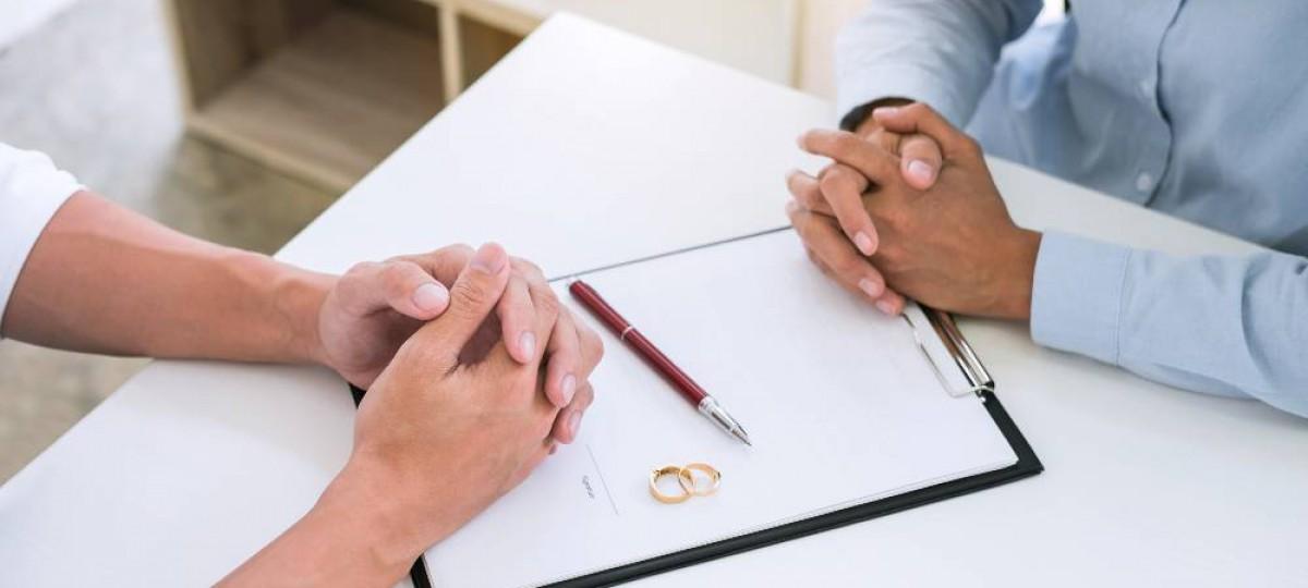 couple qui divorce devant des papiers à signer avec les alliances posées sur les papiers