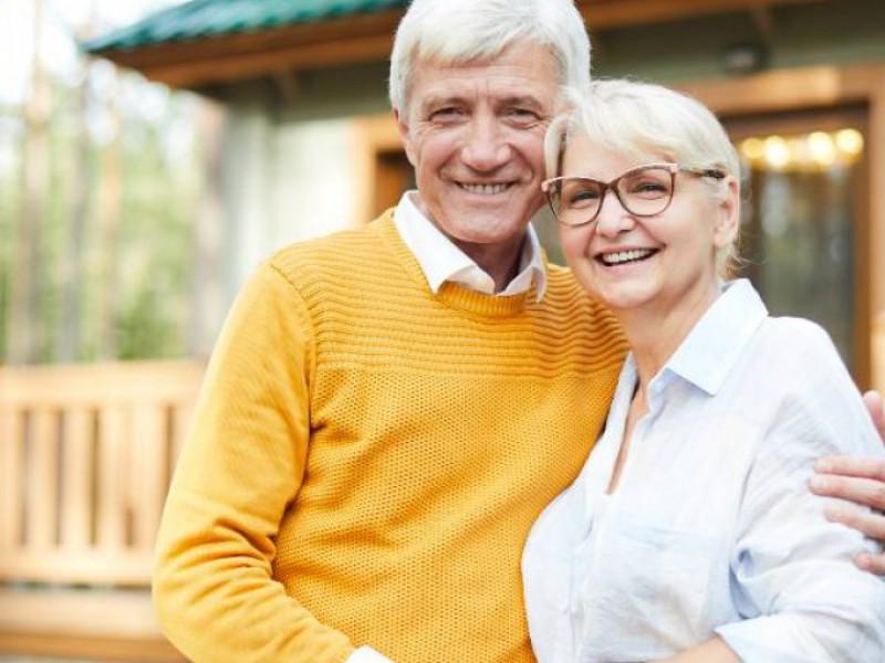 couple senior devant sa nouvelle maison