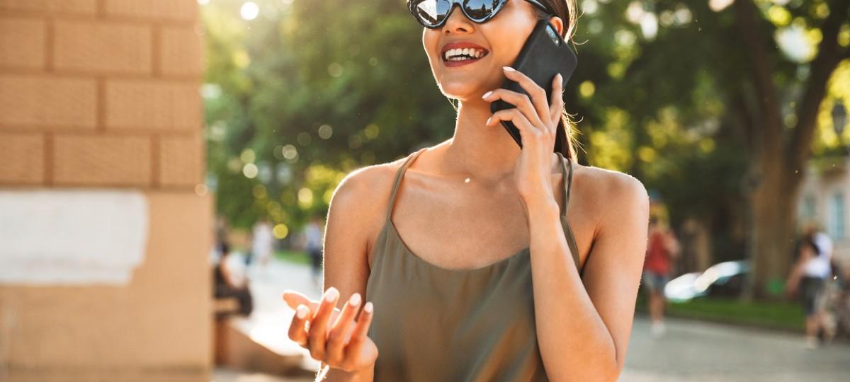 Une dame sourit au téléphone, elle vient de signer un rachat de crédits