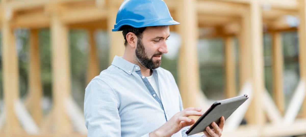 Homme tenant sa tablette numérique devant sa maison en cours de construction