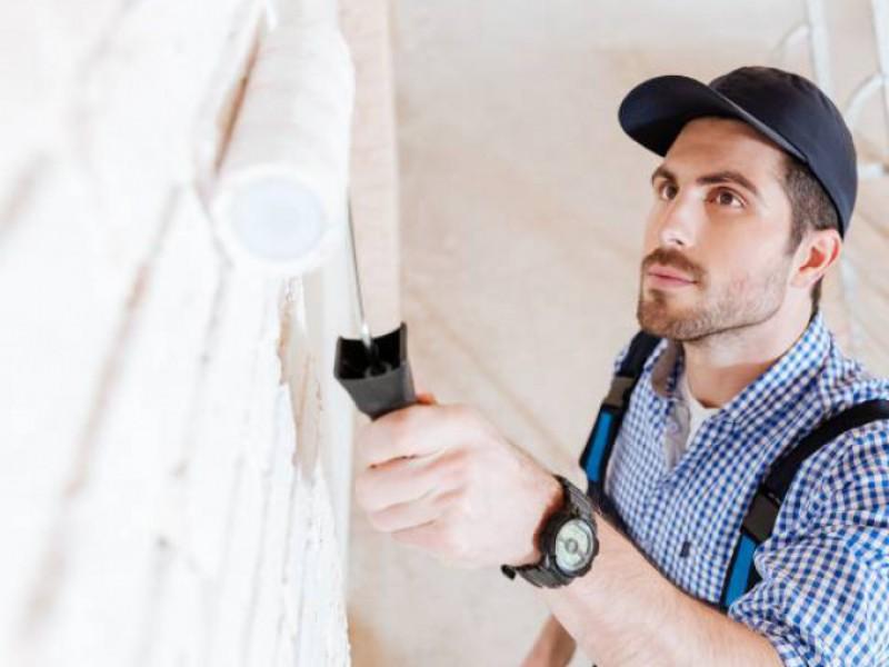 Homme peignant un mur en blanc après la pose d'une isolation et d'un revêtement décoratif