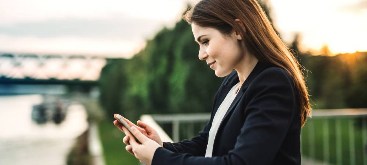 Jeune femme souriante au bord d'un fleuve faisant une simulation sur son smartphone.