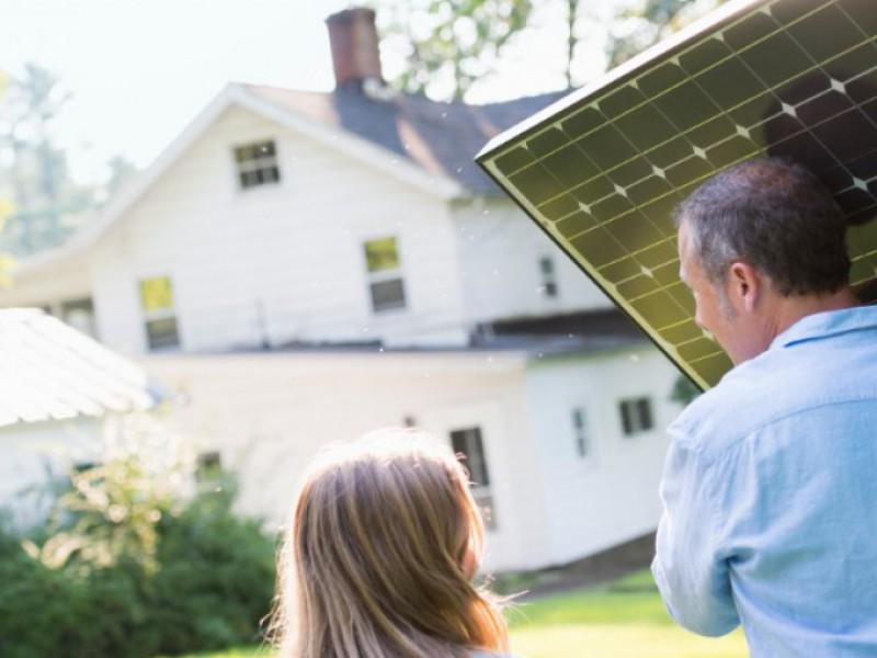 Homme portant un panneau solaire à installer sur sa maison, une petite fille l'accompagne