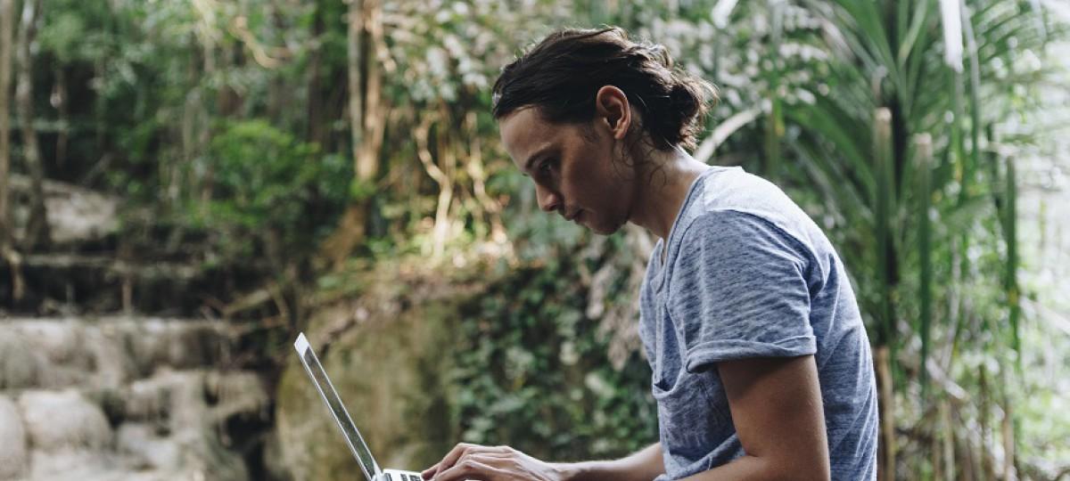 Un jeune homme est assit sur son ordinateur et s'informe sur la différence entre la renégociation et le rachat de crédits