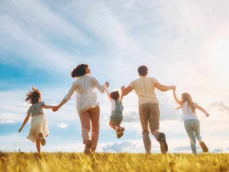 Famille heureuse courant dans un champs au soleil