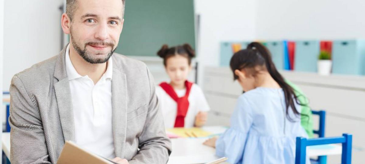 Enseignant tenant un livre devant sa classe