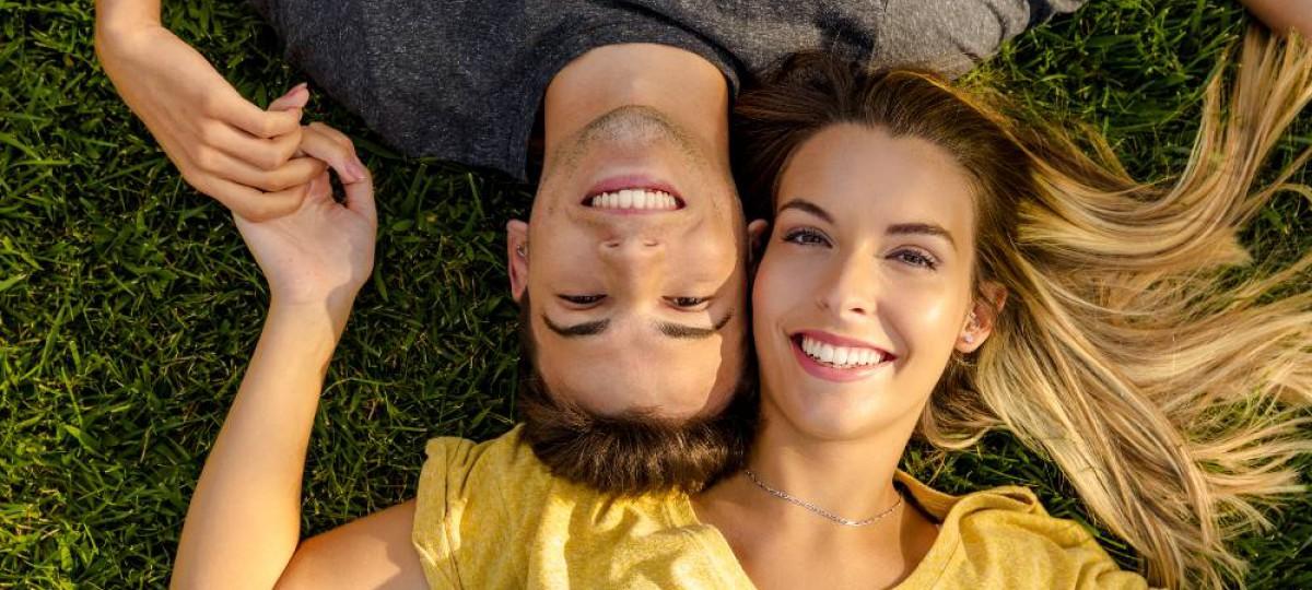 Couple heureux et souriant allongé dans l'herbe